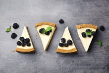 Pieces Of Delicious Cheesecake With Blackberries On Grey Background, Flat Lay