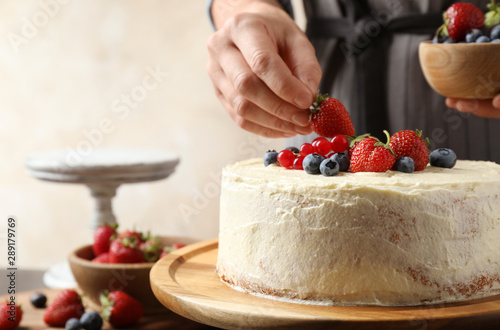 Fototapeta  Woman decorating delicious homemade cake with fresh berries at table indoors, cl
