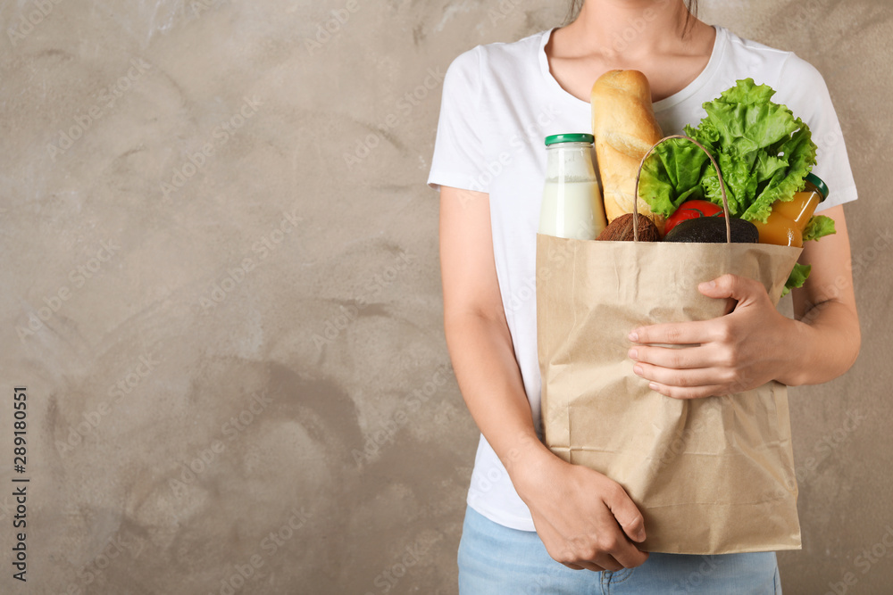 Fototapety, obrazy: Woman holding shopping paper bag with different groceries against brown background. Space for text