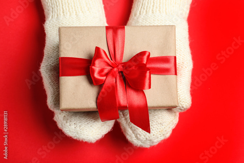 Woman holding Christmas gift on red table, top view