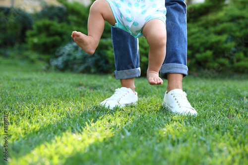 Cute little baby learning to walk with his nanny on green grass outdoors, closeu Wallpaper Mural