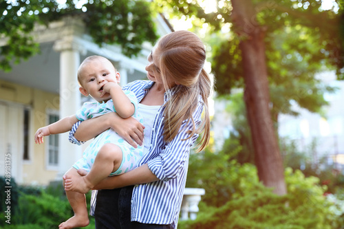 Teen nanny with cute baby outdoors on sunny day Wallpaper Mural