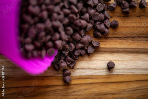 mini chocolate chips spilling out of pink silicone cup on rustic wood