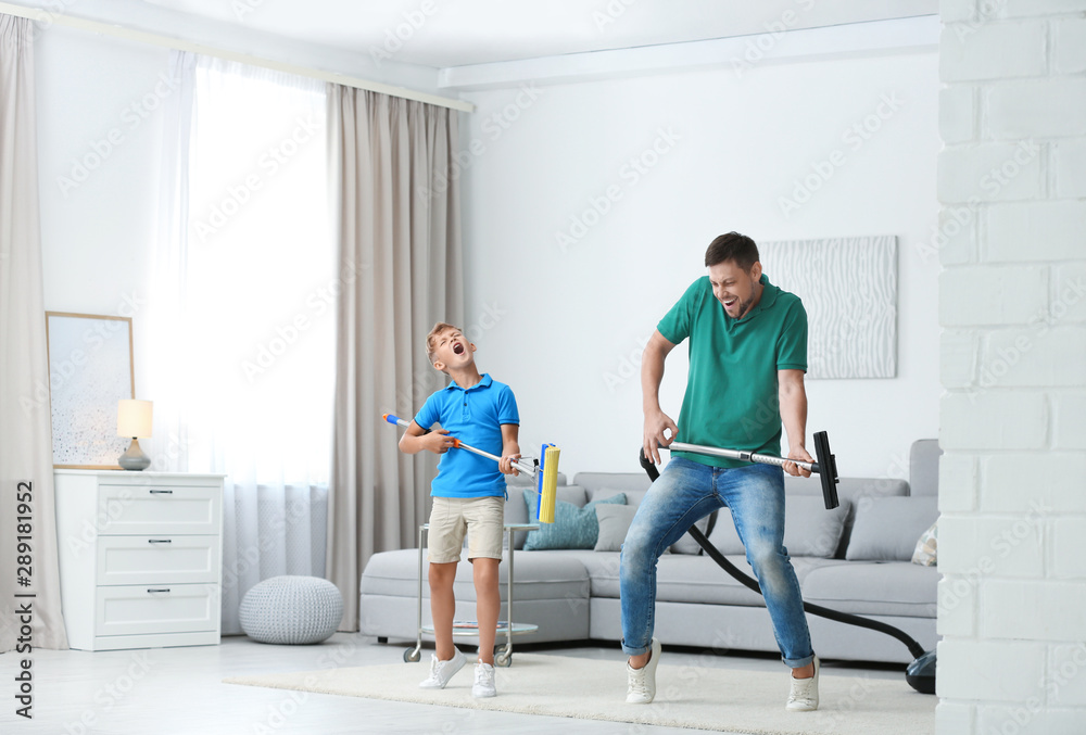 Fototapety, obrazy: Dad and son having fun while cleaning living room together