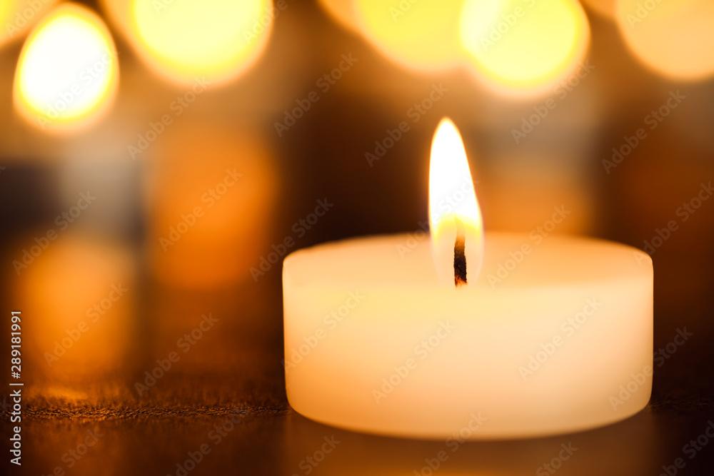 Fototapeta Burning candle on table, closeup. Funeral symbol