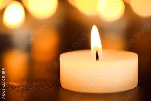 Stampa su Tela  Burning candle on table, closeup. Funeral symbol