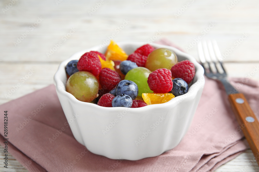 Fresh tasty fruit salad on white wooden table, closeup