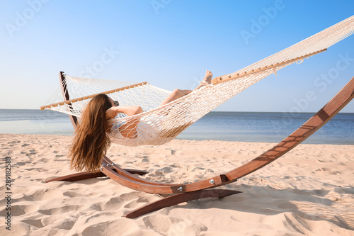 Obraz Young woman relaxing in hammock on beach - fototapety do salonu