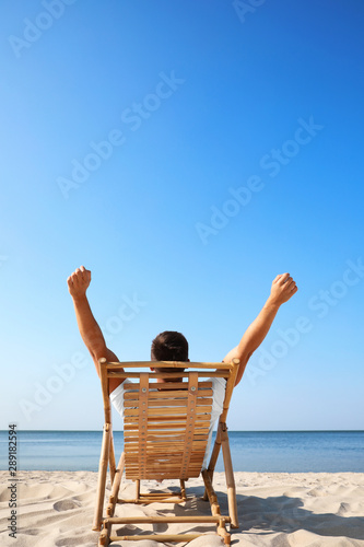 Valokuva Young man relaxing in deck chair on sandy beach