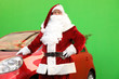 canvas print picture - Authentic Santa Claus near car with fir tree and presents against green background