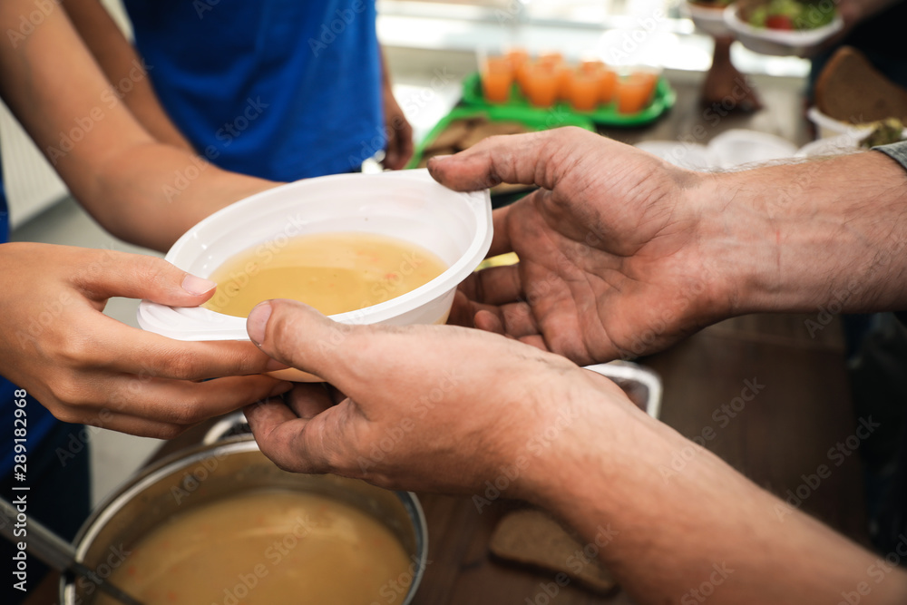 Fototapety, obrazy: Volunteer serving food to poor people in charity centre, closeup