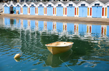 A Small Dinghy Floats In The Harbour And The Boathouses Are Reflected In The Calm Water