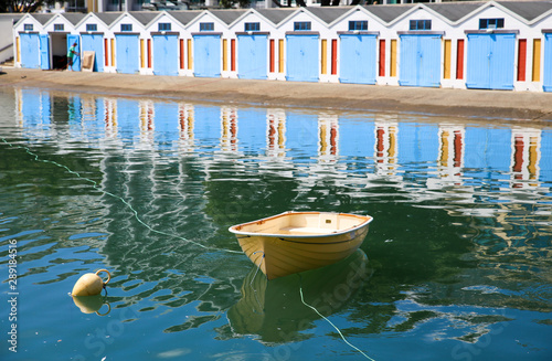 A small dinghy floats in the harbour and the boathouses are reflected in the cal Canvas Print