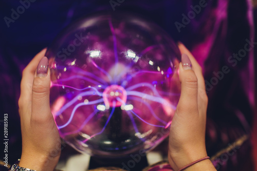 Hand touching a plasma ball with smooth magenta-blue flames. Canvas Print