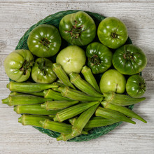 Fresh Organic Green Tomatoes And Okra In A Basket Isolated On A White Wood Board.