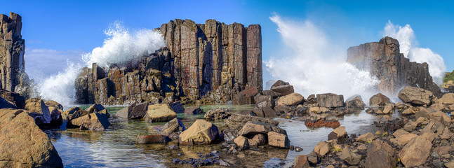 Panorama of waves breaking over basalt rock formations and rockpools at Bombo Headland quarry, New South Wales coast, Australia
