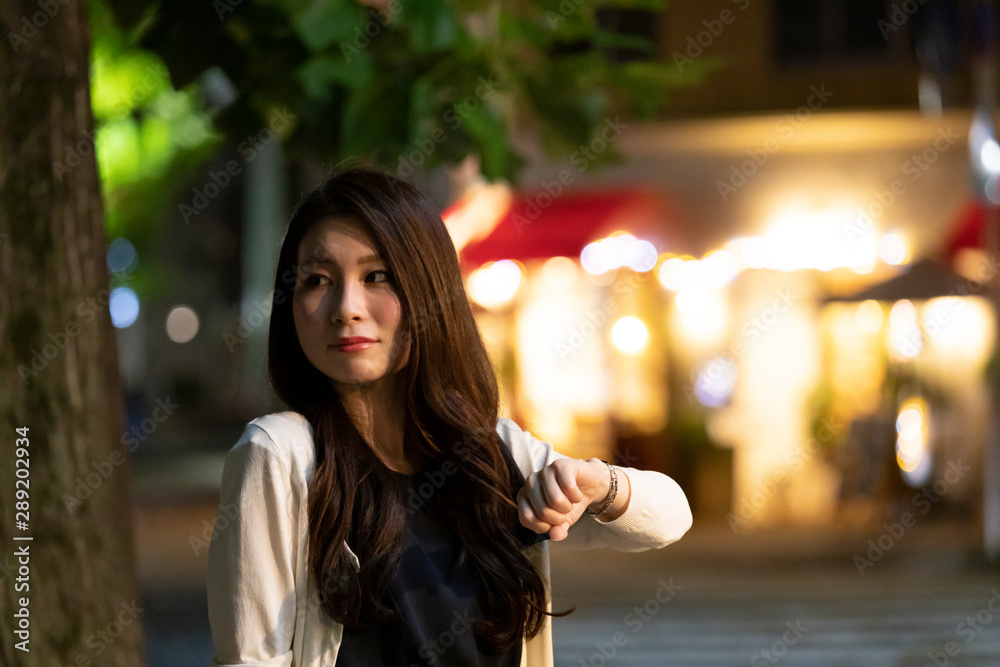 Fototapeta 夜の町並みを背景に待ち合わせをする若い女性