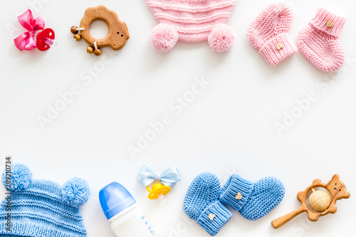 Obraz Blue and pink knitted set for kids, rattle, dummy, bottle frame on white background top view space for text - fototapety do salonu