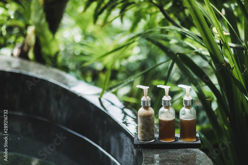 Poster Spa Different bottles for spa treatment on the edge of stone bath with tropical nature background. Wellness concept.