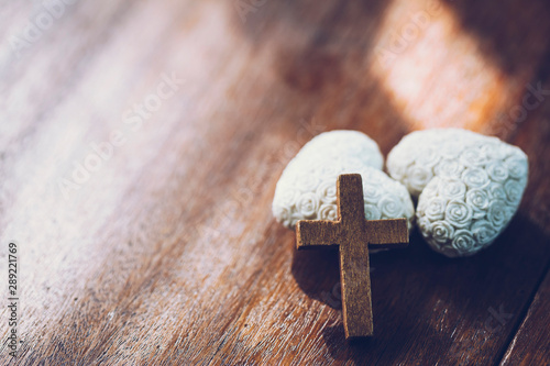 Fotografie, Obraz  wooden cross over two ceramic white heart on wooden table with copy space