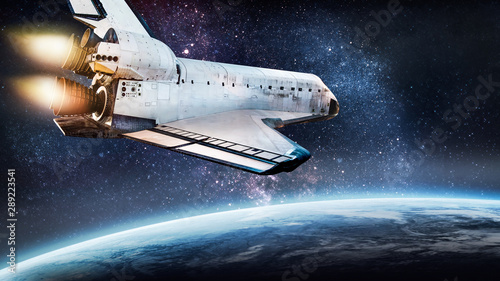 Valokuva  Space shuttle rocket in outer space over Earth planet