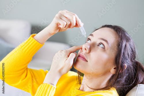 Fotografía Closeup view of young woman applying eye drop, artificial tears..