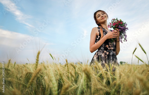 Photo  Cute attractive girl with a bouquet of colorful flowers in her hands