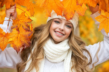 Portrait Of Beautiful Young Woman Walking Outdoors In Autumn. Girl With Autumn Yellow Leaf In Knitted Hat And Sweater.  Portrait Of A Girl With Orthodontic Appliance.