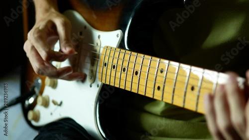 Obraz na plátne  man playing electric guitar by pick