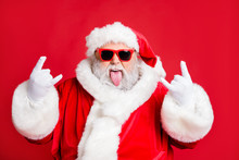 Close-up Portrait Of His He Nice Attractive Positive Playful Bearded Santa Having Fun Leisure Showing Horns Symbol Sign Heavy Metal Fest Isolated Over Bright Vivid Shine Red Background