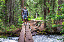 Mountain River Stream With Man Crossing Standing In Rocky Mountains In Summer Of 2019 On Conundrum Creek Trail In Aspen, Colorado With Wooden Bridge