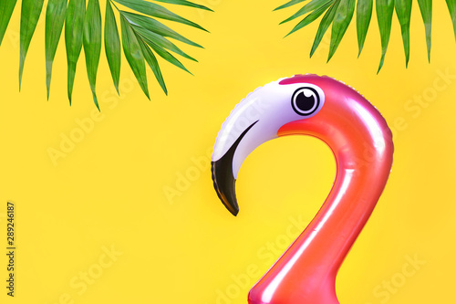 Foto op Aluminium Flamingo Summer fun concept with pink inflatable flamingo head on a yellow background with copy space