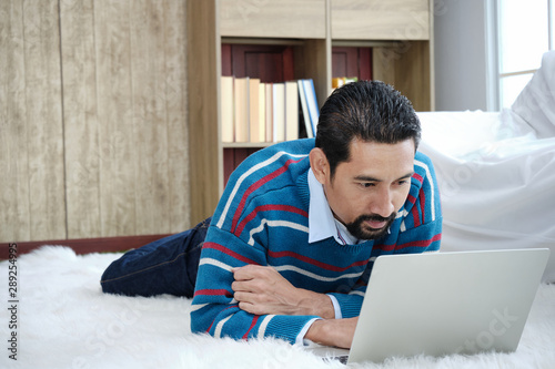 Fototapeta  Adult businessman looks dignified and riches lying on the wool rug with a laptop computer in cozy for holidays within the living room