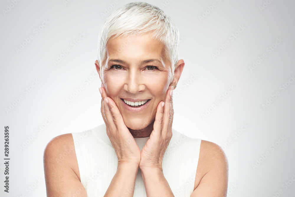 Fototapeta Beautiful smiling senior woman with short gray hair posing in front of gray background. Beauty photography.