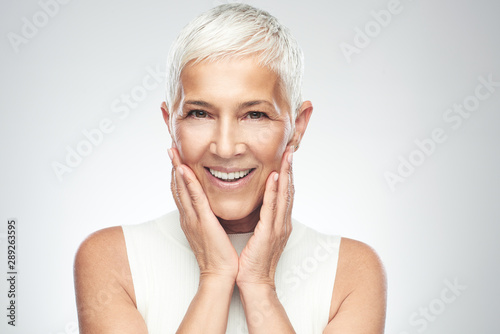 Beautiful smiling senior woman with short gray hair posing in front of gray background Fototapet