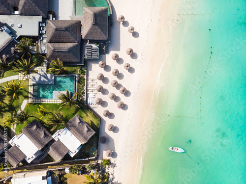 Fotomural Aerial view of beautiful tropical beach front hotel resort with swimming pool, palm leaves umbrellas and turquoise sea