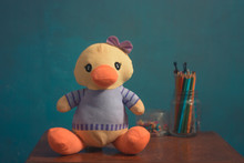 Stuffed Duck, Toy For Children And Babies On Brown Wooden Desk With Blue Background.