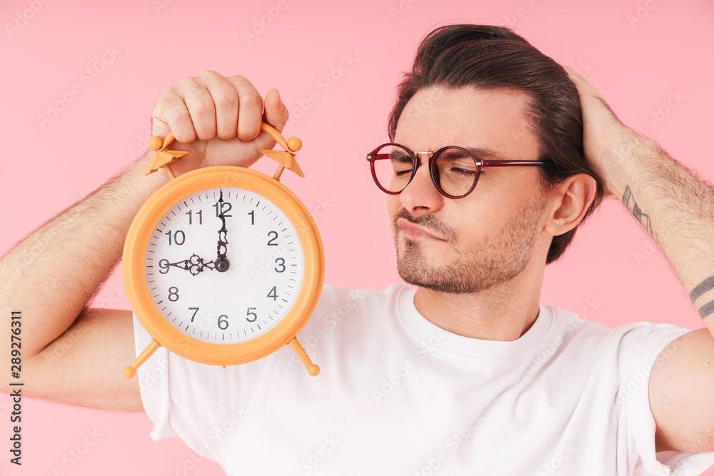 Fototapeta Image of sleepy handsome man wearing eyeglasses holding and looking at desk alarm