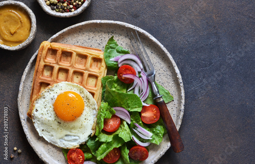 Obraz na plátně  Belgian waffles with egg and salad for breakfast in a plate on the kitchen table