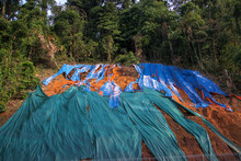 Slope Protection With Huge Plastic Sheet To Avoid Soil Erosion When It Rains. Colorful Pieces Of Plastic Cover Lying On The Ground Under The Trees.