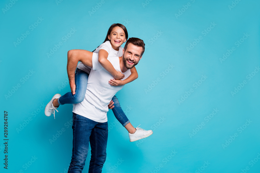 Fototapeta Portrait of cheerful people laughing piggyback wearing white t-shirt denim jeans isolated over blue background
