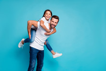 Portrait Of Cheerful People Laughing Piggyback Wearing White T-shirt Denim Jeans Isolated Over Blue Background