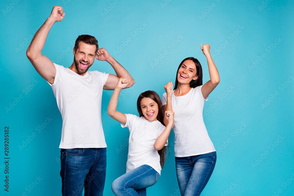 Fototapeta Portrait of cheerful family having brunette hair raising fists screaming yeah celebrating victory wearing white t-shirt denim jeans isolated over blue background