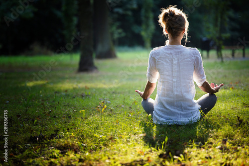 In de dag School de yoga young woman practicing yoga and meditating in the forest