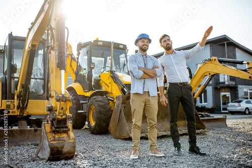 Stampa su Tela  Builder with a sales consultant at the shop with heavy machinery