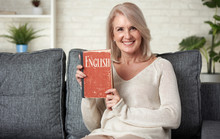 Beautiful 50 Years Old Woman Reading An English Textbook