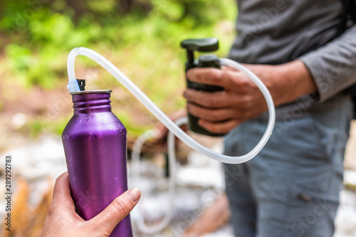 Fotografía Man and woman couple using water filter on hiking trail river in Colorado to pur