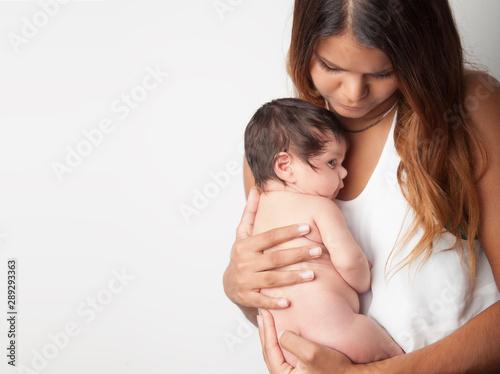 Australian mother holding newborn baby girl on white background Wallpaper Mural