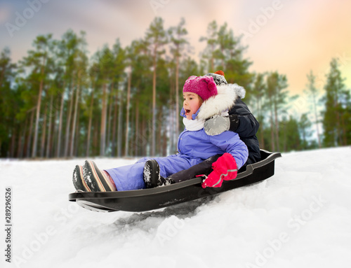 childhood, sledging and season concept - happy little kids sliding on sled down snow hill in winter over forest background