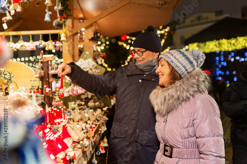 shopping, winter holidays and people concept - happy senior couple at christmas market souvenir shop stall on town hall square in tallinn, estonia - 289302551